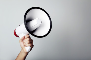 Female hand holding megaphone on grey background Wall mural