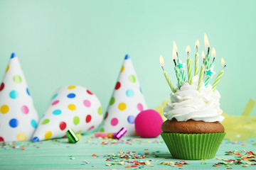 Cupcake with candles, blowers and paper caps on green background