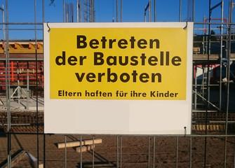 Baustellenschild mit deutschem Text: Betreten der Baustelle verboten, Eltern haften für ihre Kinder.