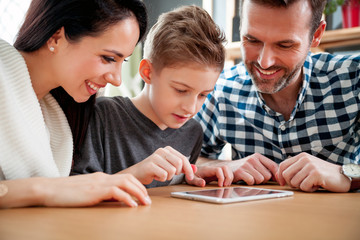 Happy family using tablet together at home