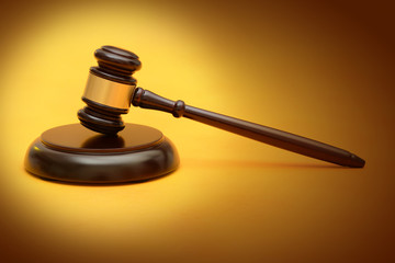 Wooden Judge Gavel on yellow background law concept