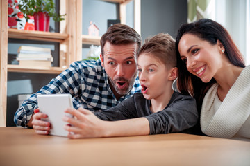 Happy family using digital tablet taking selfie photo at home