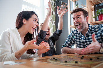 Family playing board game at home, boy throwing elements after winning