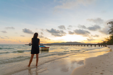 young beautiful woman watching sunrise on tropical island koh rong sanloem with boat in background