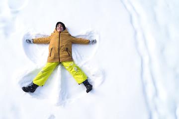 boy makes snow angel, copy space