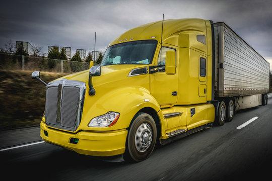 Big yellow 18 wheeler truck on highway