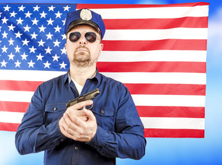 A male policeman holding a gun over a US flag satin - a studio shoot