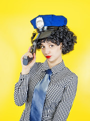 Portrait of a police girl with a gun. Thoughtful policeman in retro style.