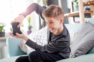 Excited young boy playing game on the console at home