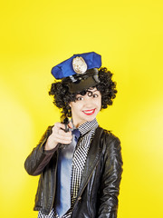 Beautiful woman holding a gun - Super cops, portrait on a yellow background