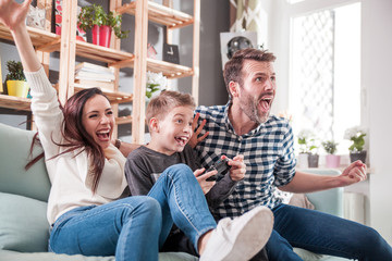 Excited family playing video game on the console at home