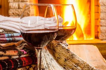 Glasses of red wine against cozy fireplace background; winter vacation.