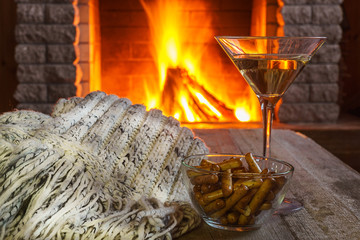 Glass of martini wine against cozy fireplace background, winter vacation.