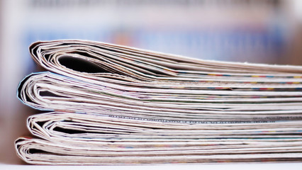 Newspapers folded and stacked in a pile, selective focus
