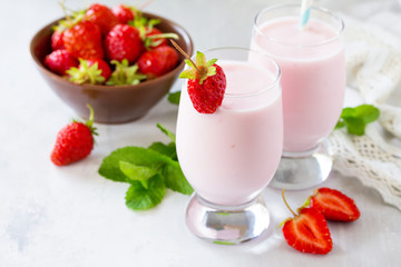 Fresh strawberry smoothie and fresh strawberries on a gray stone or slate background. Vegan dish. Proper nutrition. Healthy lifestyle.