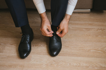 A man or businessman in a suit ties up shoelaces on black leather shoes on a parquet background