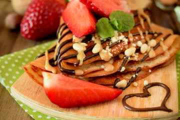Crepes decorated with nuts, chocolate, fresh strawberries and mint