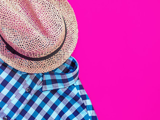 A straw hat and a blue men's shirt made from organic cotton are on a purple background. Image for advertising clothing store, discounts, fashion blog