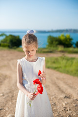 pensive little girl wearing white dress with a bouquet of red poppies outdoors in spring