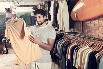 Adult male consumer choosing colorful dress in the boutique