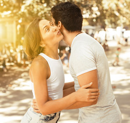 positive man and woman meeting and kissing on the street