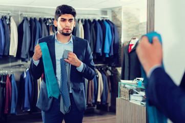 Man is picking up tie for jacket in front of the mirror