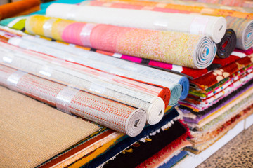 Stack of traditional  colorful carpets in carpet shop