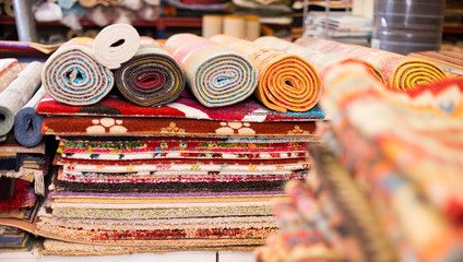 Carpets of different colours in stack at carpet store