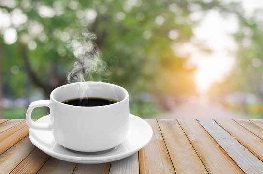 coffee cup with smoke on wood table with green nature blur bokeh background in the park at morning and sunlight.