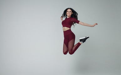 Portrait of fit and sporty young woman jumping on grey background.