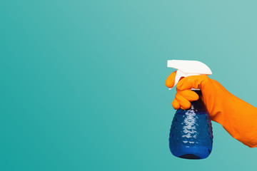 A hand in glove holding spray of cleaning fluid Wall mural