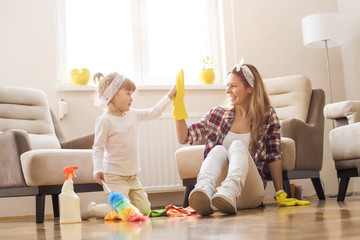 Obraz Daughter and mother cleaning home together and having fun. - fototapety do salonu