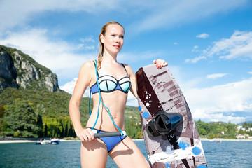 Junge hübsche Frau fährt wakeboard am Gardasee, auf dem Wasser Meer. Sie freut sich auf den nächsten Wellenritt im Sommer