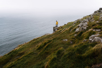 Young adult male wearing a yellow rain jacket standing on a overgrown cliff overlooking the overcast atlantic ocean in Scotland, UK