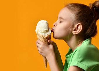Pretty baby girl kid kiss vanilla ice cream in waffles cone