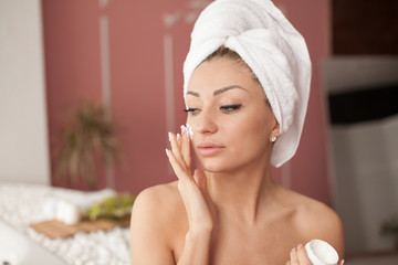 Young woman with flawless skin, applying moisturizing cream on her face. Photo of woman after bath in white bathrobe and towel on white background. Skin care concept