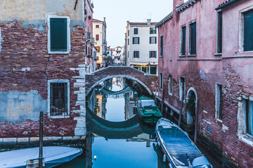 Typical Venetian canal with red houses at evening, Venice, Italy