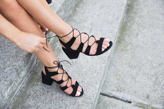 Tanned young woman's legs in black suede leather sandals