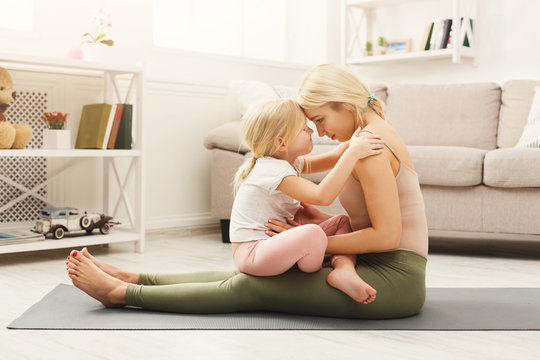 Happy mother and daughter hugging while home yoga class