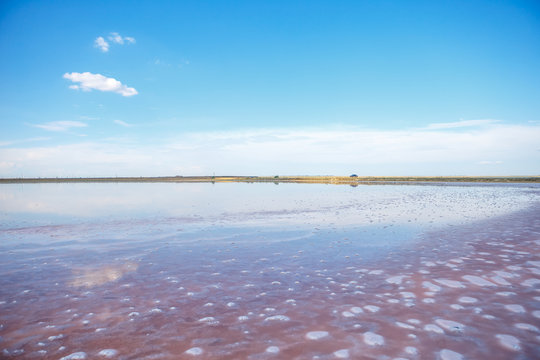 Panoramic view of Pink Salt Lake in . This lake turns pink in summer cause of an algae with red pigments. Blue sky, horizon