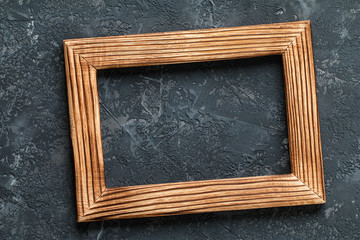 Classic wooden frame on dark stone background.