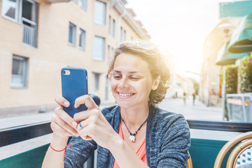 young beautiful happy woman girl sitting in cafe in european city with mobile phone in hands