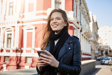 Excellent day for adventures. City portrait of attractive european girl walking in street, holding smartphone and looking aside while waiting for her boyfriend at their usual meet spot