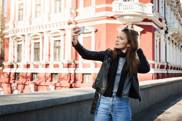 I was born to by stylish. Outdoor portrait of beautiful woman standing in city centre, posing while holding smartphone and taking selfie, wearing trendy clothes on date with boyfriend