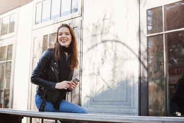 Beautiful concrete jungles. Outdoor shot of smiling attractive girl walking in city, sitting near cafe, laughing over funny guy who tries impress her, holding smartphone. Sister waits for her sibling