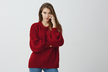 Girl is worried while waiting for results of test. Portrait of good-looking feminine woman in red loose sweater biting fingernails while looking at camera with thoughtful and serious expression