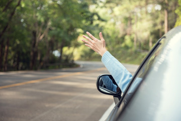 Close up woman hand with arm raised relaxing and enjoying road trip. she happy driver in car on road in nature. copy space.