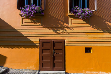 Wooden door and windows on old rustic orange house in Romanian city Sighisoara in Transylvania