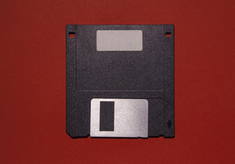 An obsolete floppy disk on a red background. You can write something on the blank label.