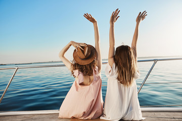 Outdoor back shot of two young female on luxury vacation, waving at seaside while sitting on yacht. Best friends are waiting for waiter to order some drinks as they are sailing on cruise ship